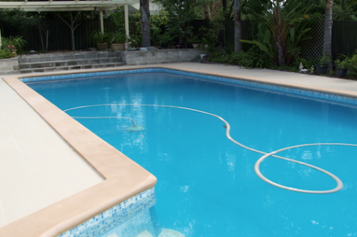 cap 1 - fibreglass lined pool recoated with Pacific Blue and old pebble deck (coping) resurfaced with Riversand