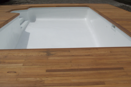 cap 9 - old marblesheen line pool recoated with white new tiles and a new timber deck