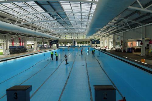 Poolpainters team resurfacing Olympic pool undercover